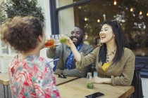 Amici entusiasti sorridenti che tostano bicchieri di succo fresco al caffè marciapiede — Foto stock