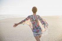 Mulher despreocupada, andando com os braços estendidos na praia de verão — Fotografia de Stock