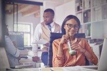 Портрет усміхнений впевнено бізнес-леді пити зелений коктейль в офісі — стокове фото