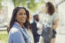 Femme de portrait souriante, confiante dans le parc ensoleillé — Photo de stock
