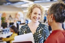 Donne di affari sorridente che comunicano all'ufficio moderno — Foto stock