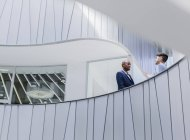 Businessmen talking on architectural, modern office balcony — Stock Photo