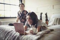 Smiling couple se détendre, boire du café et à l'aide de tablette numérique sur lit — Photo de stock