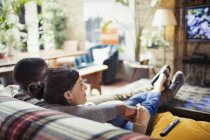 Affectionate young couple watching TV on living room sofa — Stock Photo