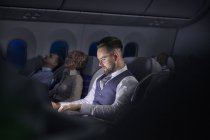 Businessman working on laptop on night airplane — Stock Photo
