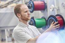 Мужчина меняет катушку на заводе волоконной оптики — стоковое фото