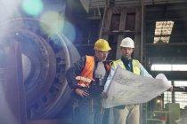 Инженеры рассматривают чертежи на сталелитейном заводе — стоковое фото