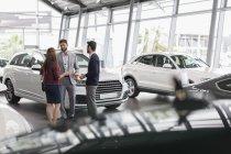 Vendedor de coches hablando con un par de clientes en la sala de exposición concesionario de coches - foto de stock
