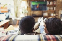 Young couple relaxing, watching TV on living room sofa — Stock Photo