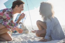 Madre e figlia che giocano nella sabbia sulla soleggiata spiaggia estiva — Foto stock