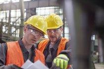 Рабочие обсуждают документы на заводе — стоковое фото