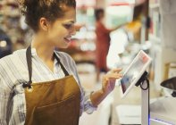 Female cashier using touch screen cash register in grocery store — Stock Photo