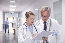 Ärzte mit Klemmbrett machen Runde, reden im Krankenhausflur — Stockfoto
