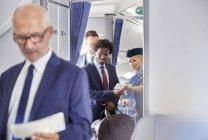 Стюардесса, помогая бизнесмен с посадочный талон на самолете — стоковое фото