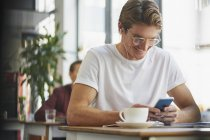 Smiling man with headphones using cell phone and drinking coffee in cafe — Stock Photo
