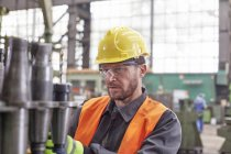 Focused male worker examining steel parts in factory — Stock Photo