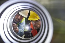Serious male engineers with flashlights examining steel pipe — Stock Photo