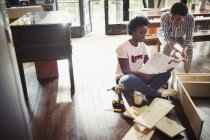 Women reading instructions, assembling furniture — Stock Photo