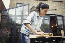 Junge Frau misst Holz auf Terrasse — Stockfoto