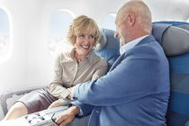 Affectionate mature couple holding hands on airplane — Stock Photo