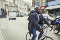 Businessman commuting, riding bicycle on urban street — Stock Photo
