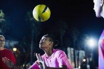 Giovane giocatore di calcio femminile testa la palla sul campo di notte — Foto stock