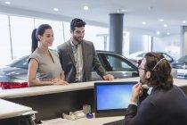 Un paio di clienti che parlano con receptionist maschile alla scrivania in concessionaria auto showroom — Foto stock