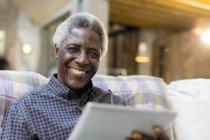 Portrait souriant, confiant homme senior à l'aide de tablette numérique sur canapé — Photo de stock