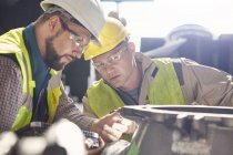 Steelworkers examining steel part in steel mill — Stock Photo