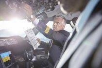 Männliche Piloten mit Zwischenablage Vorbereitung, Anpassung der Instrumente im Flugzeug-cockpit — Stockfoto