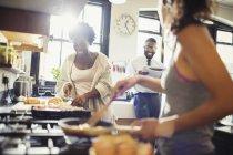 Friend roommates cooking breakfast in kitchen — Stock Photo