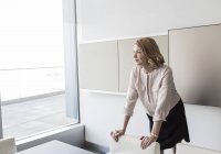 Pensive businesswoman looking out office window — Stock Photo