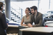 Couple customers talking to receptionist at desk in car dealership showroom — Stock Photo