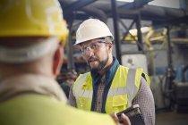 Steelworkers talking in steel mill — Stock Photo