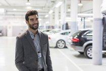 Venditore di auto sorridente ritratto che osserva via nel negozio di riparazione di auto concessionaria auto — Foto stock