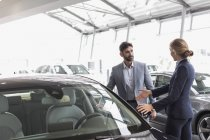 Car saleswoman showing new car to male customer in car dealership showroom — Stock Photo