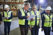 Manger and workers with clipboard talking in distribution warehouse — Stock Photo
