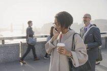 Silhouette businesswoman talking on cell phone and drinking coffee on urban bridge, London, UK — Stock Photo