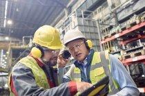 Steelworkers wearing ear protectors using digital tablet in steel mill — Stock Photo