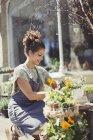 Female florist arranging display at sunny flower shop storefront — Stock Photo