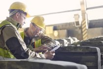 Steelworkers using digital tablet in steel mill — Stock Photo