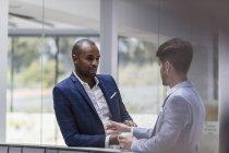 Два счастливых бизнесмена разговаривают в офисе — стоковое фото