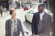 Casal sorridente viajando com bicicleta na ensolarada rua urbana — Fotografia de Stock