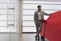 Продавец автомобилей стоит у крытого автомобиля в салоне автосалона — стоковое фото