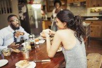 Couple de boire du café et de manger le petit déjeuner à table — Photo de stock