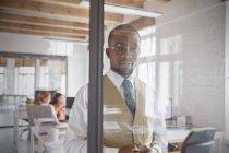 Portrait homme d'affaires confiant à la fenêtre dans le bureau — Photo de stock