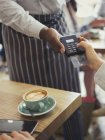 Customer paying waiter with credit card reader at cafe table — Stock Photo