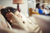 Jovem relaxante com a mão no cabelo no sofá — Fotografia de Stock