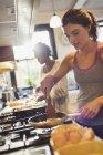 Frau kocht Eier auf Herd in Küche — Stockfoto