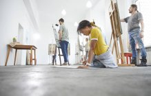 Female artist sketching on floor in art class studio — Stock Photo